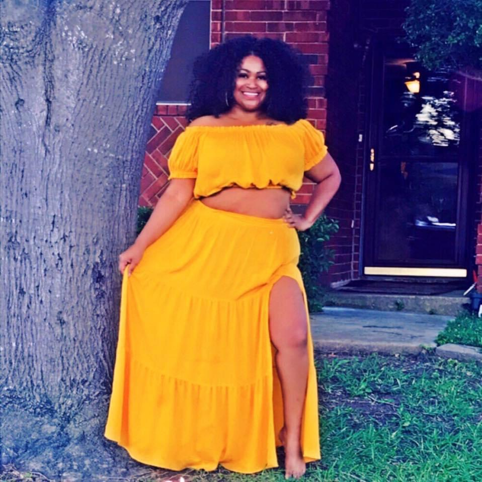 Mommy Magick founder and CEO poses in a two-piece yellow skirt outfit.