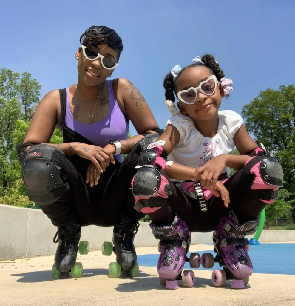 Mother and daughter squad with roller skater on and sunglasses on at tennis court