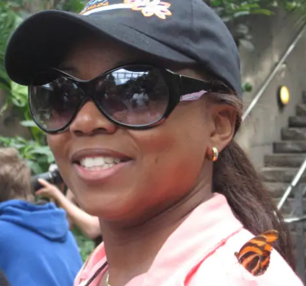 Miriam Carey, a black woman, is seen smiling in dark baseball and and sunglasses with a monarch butterfly on her shoulder.
