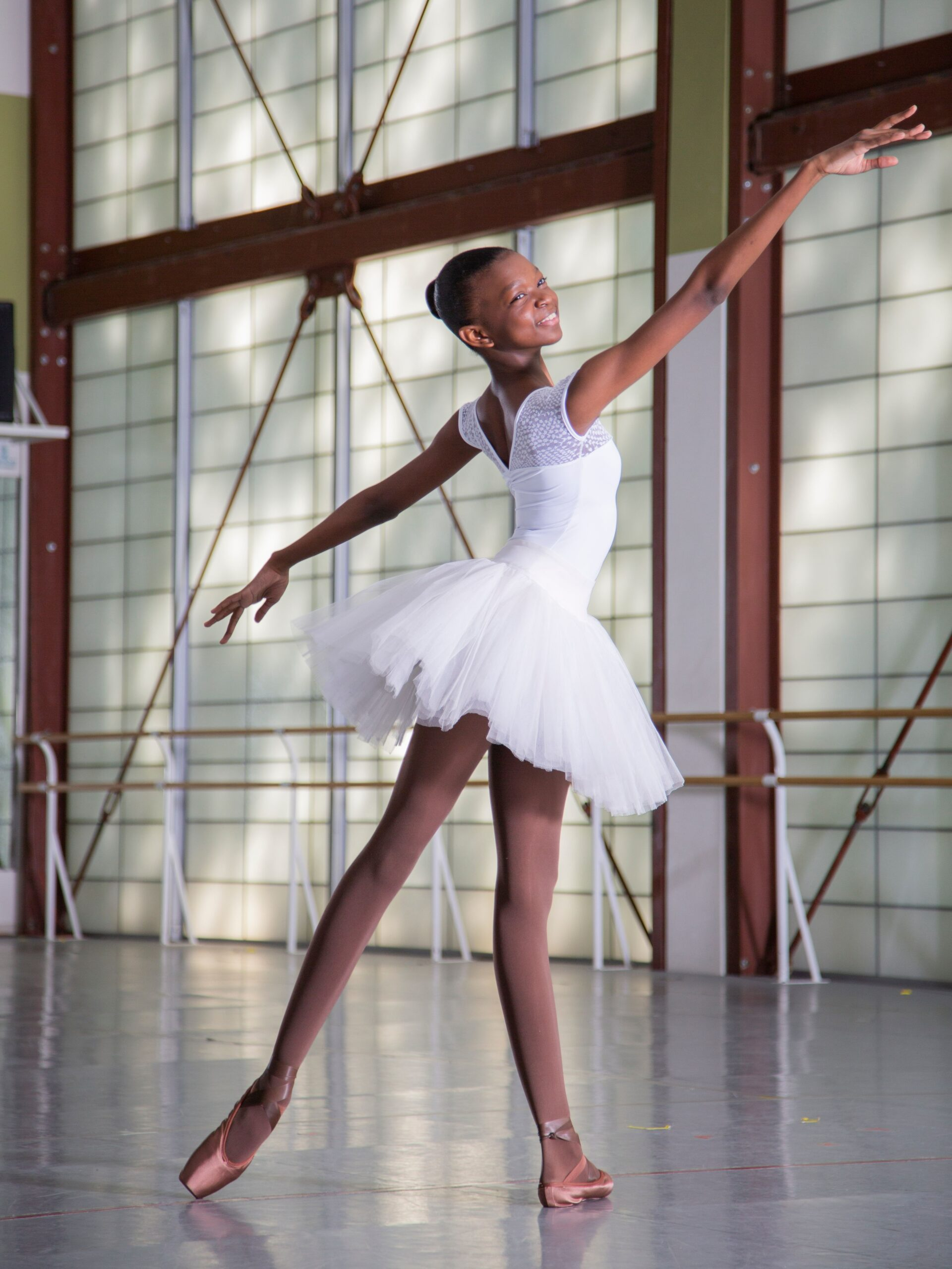 Black ballerina in while tutu outfit poses with tights and shoes that match her darker complexion.