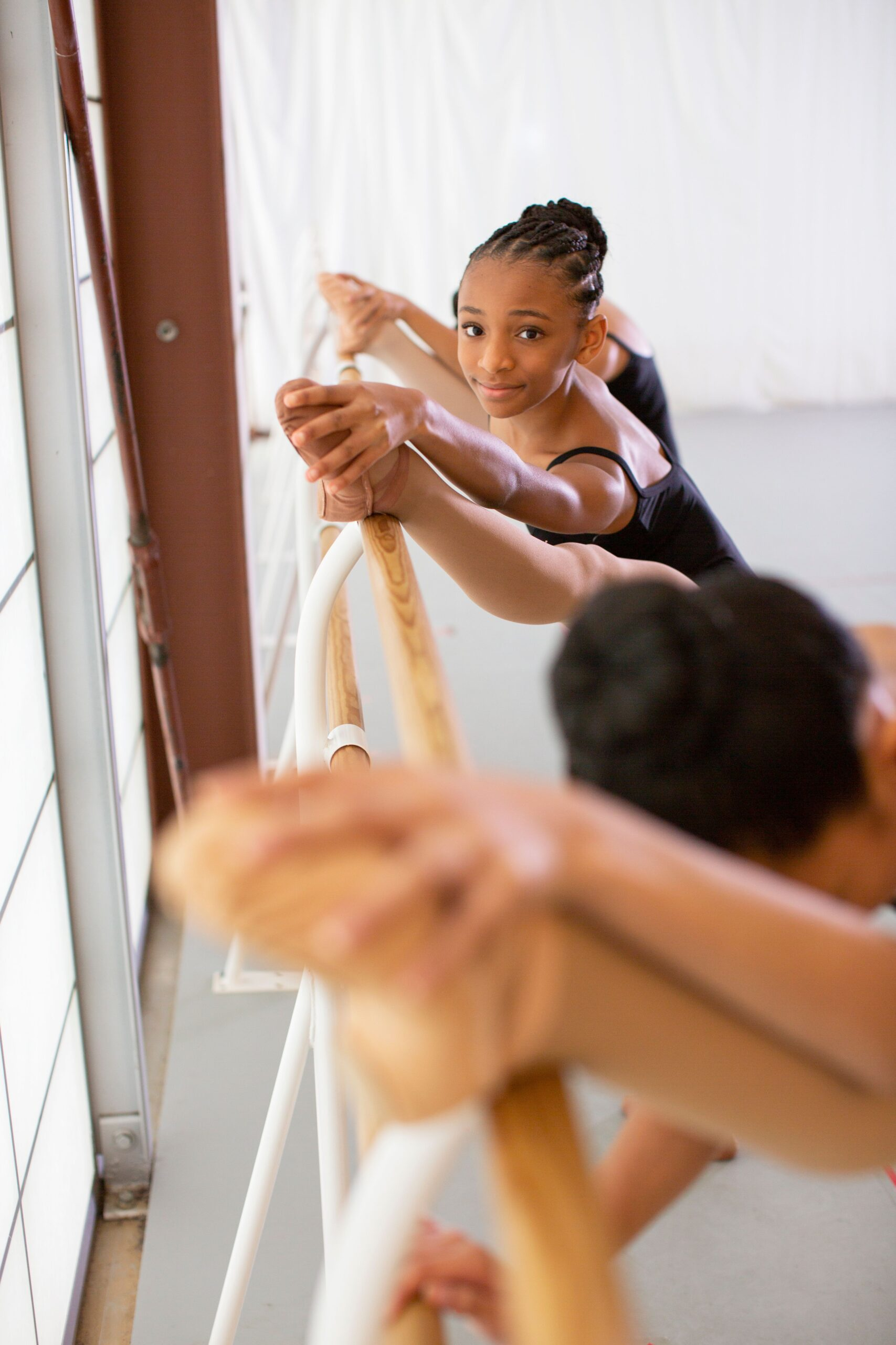 Photo of multiple young ballerina dancers at the bar, with the photo focused on the one in the center. She is a young black girl with her hair braided into a bun.