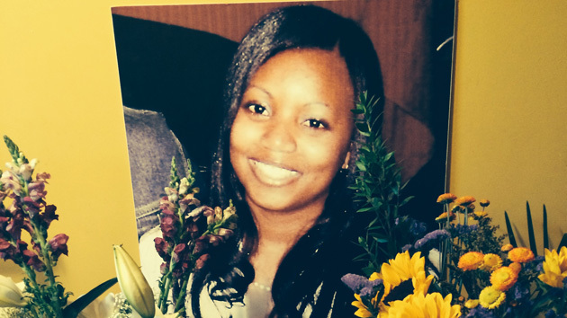 Memorial photo of Miriam Carey, a black woman, surrounded by flowers.