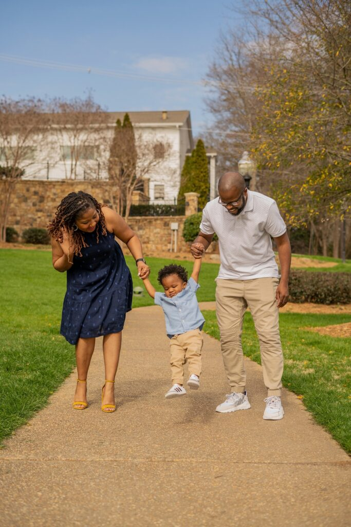 Brittany and her husband Anthony are swinging their son Lennox by the hands. They are walking in a park on a sunny day. Lenny looks somewhat stoic but both Brittany and Anthony are smiling while looking down at him.