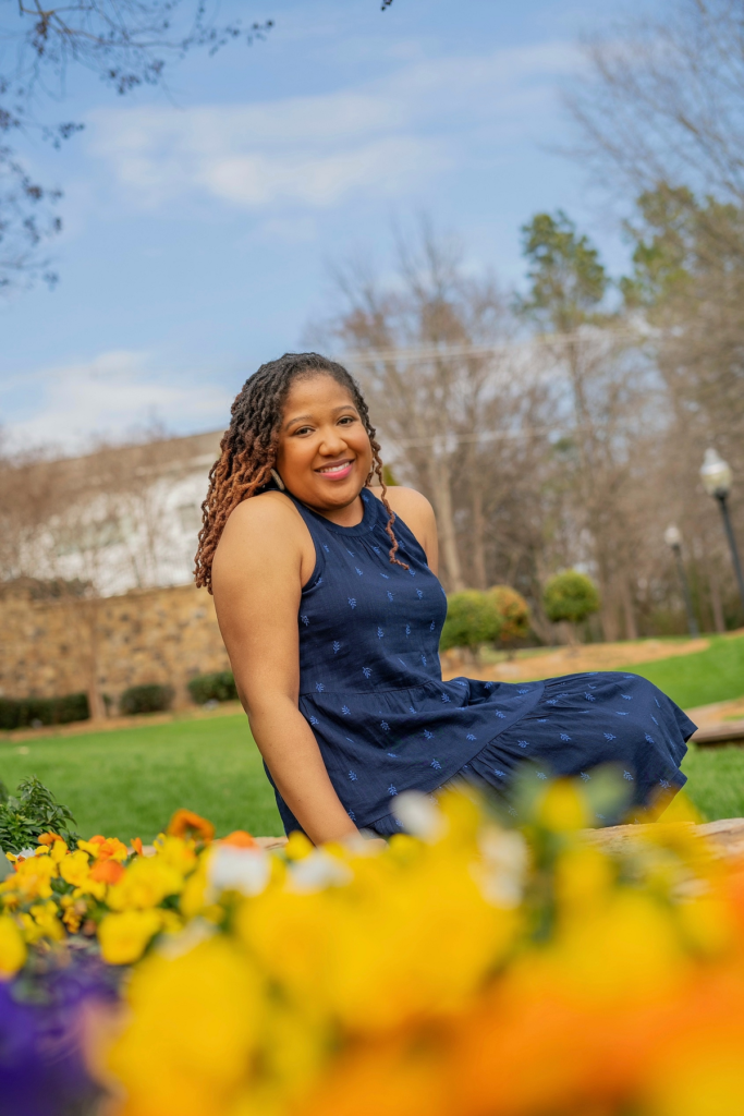 Brittany is sitting down on a bench at a park. She is wearing a navy blue sleeveless dress and her locs are hanging down. There are flowers in front of her and she is smiling.