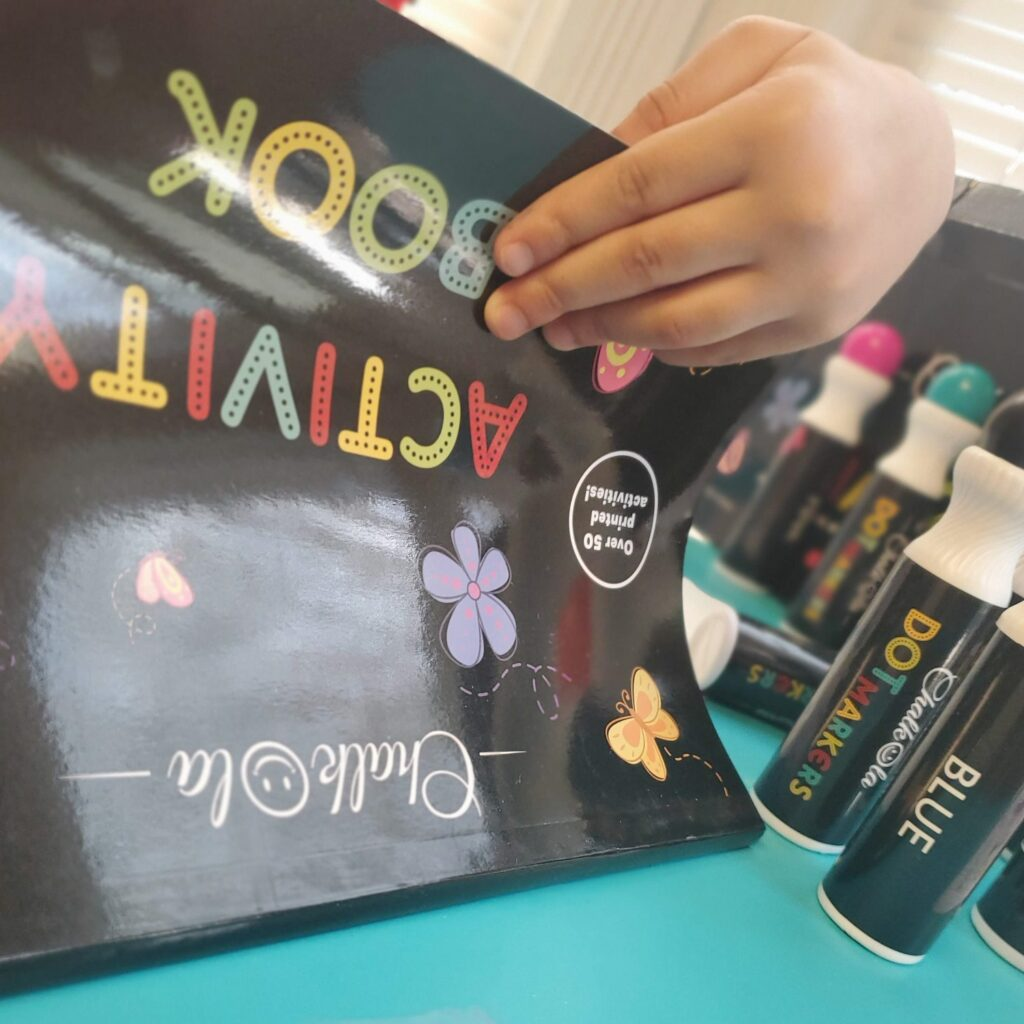 Close up of young hand opening a black Chalkola activity book with dot markers seen in the background.
