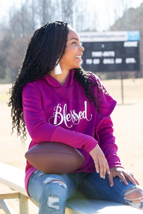 Black woman in purple hooded sweatshirt with the word Blessed written in curved words in the center sits at an empty football field cradling a football and looking out into the field. Scoreboard is seen behind her.