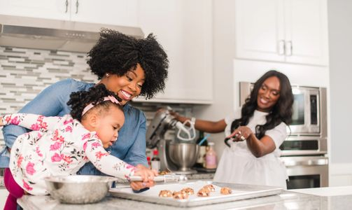 A black woman with a curly fro holds her daughter as she places cookies on baking sheet, with another Black woman with long dark hair looking on in the background.