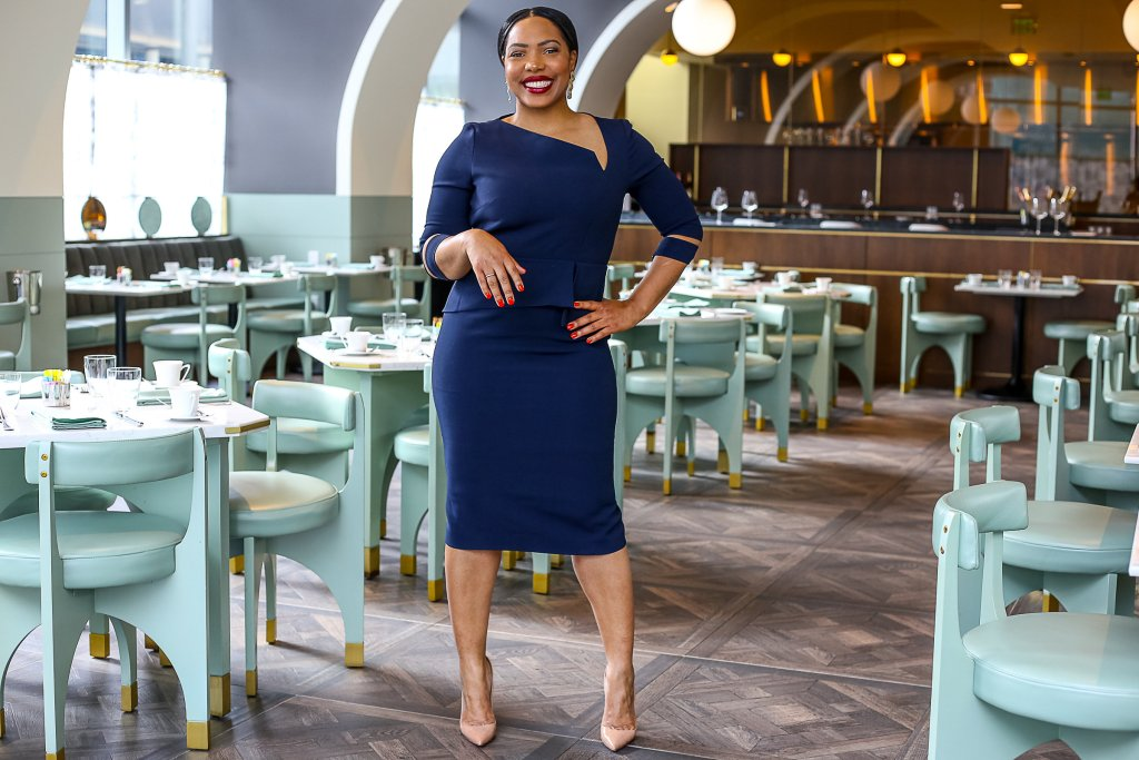 Charlene Lawson stands in a classy navy blue dress in an empty yet formal dining setting. She has one hand on her hip and is smiling with her hair slicked back.