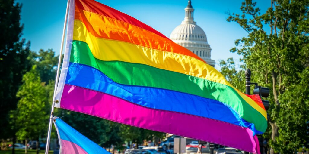 Rainbow Pride flag flies in front of the U.S. Capitol Building on a sunny day.