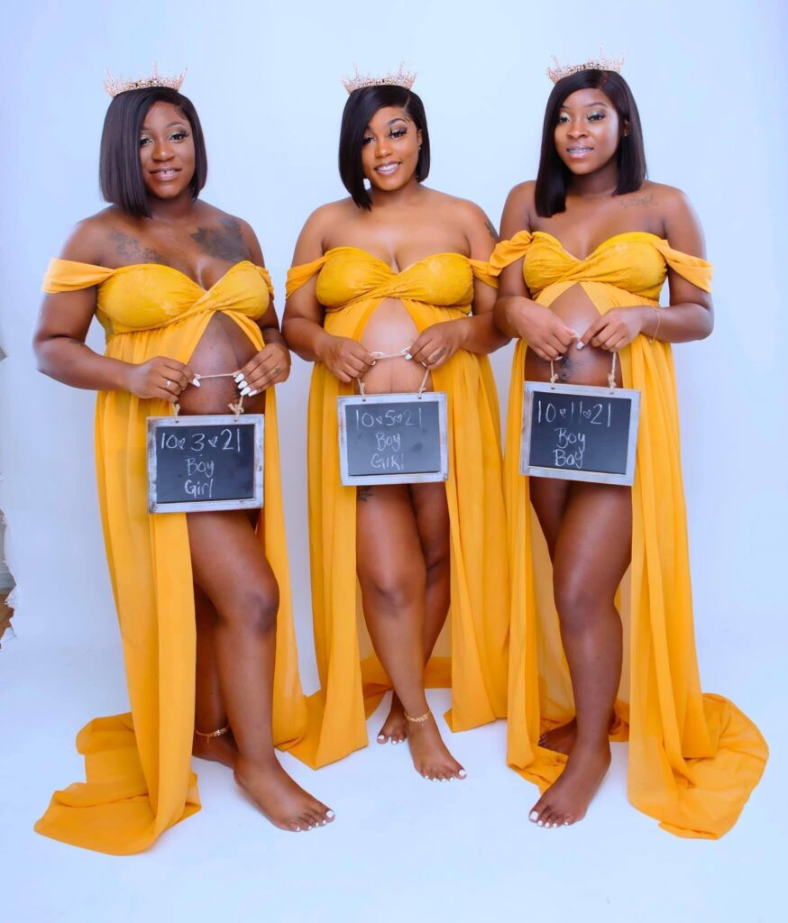 Three women dressed in identical yellow dresses with their belly bumps exposed wear crowns and matching bob haircuts.