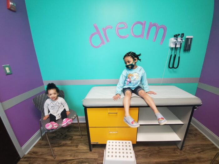 Two young black girls sit in a pediatrician office with brightly colored walls, one with the word dream written in deep purple.