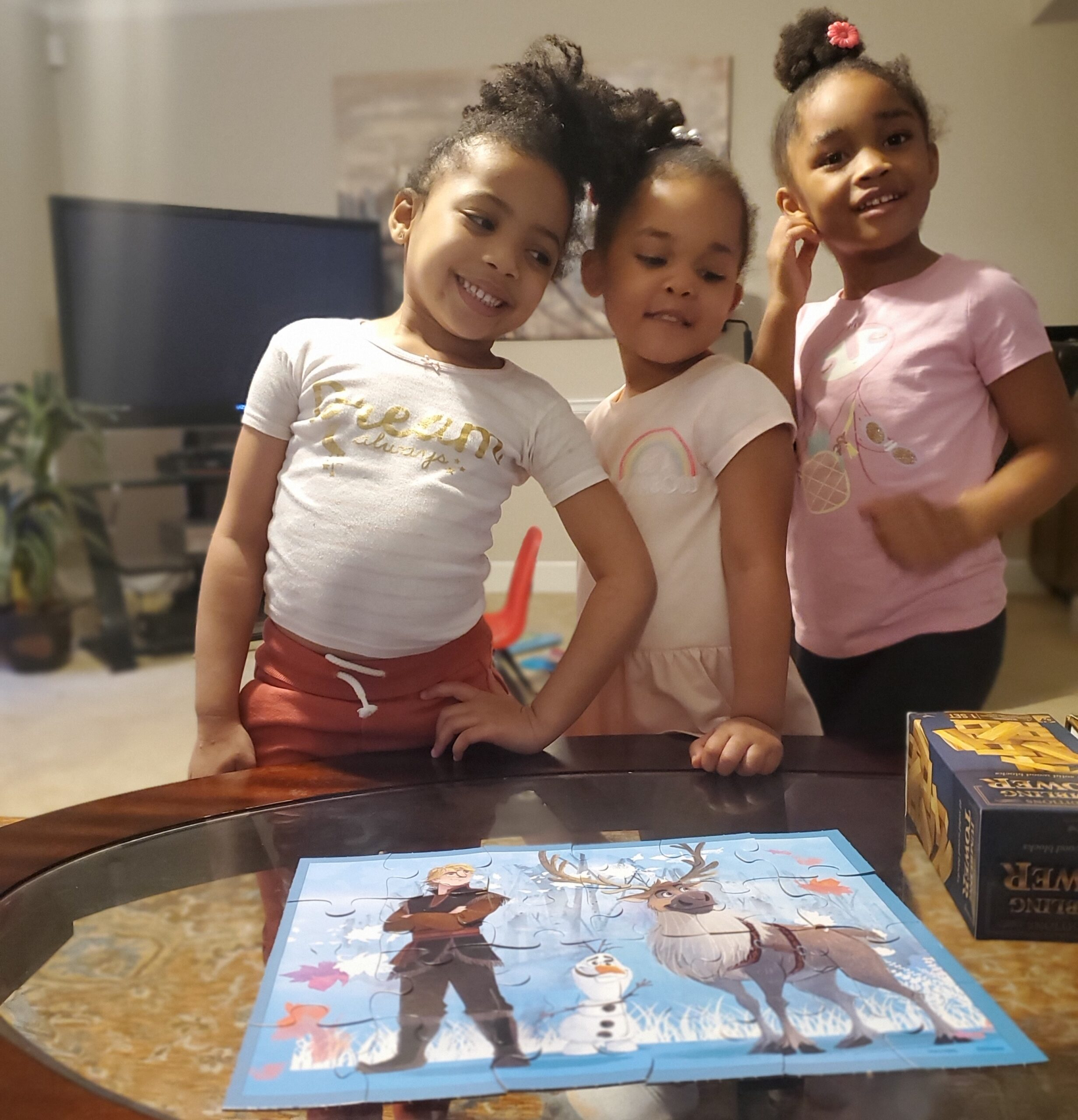 Three young Black girls stand in a living room, all smiling in front of a puzzle