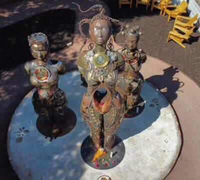 metal statue of three women stands on round, concrete platform